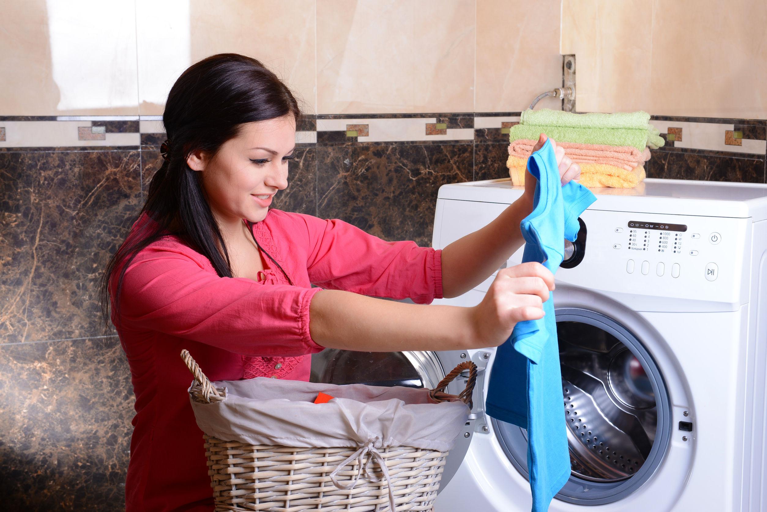 Жінка пере речі у пральній машині