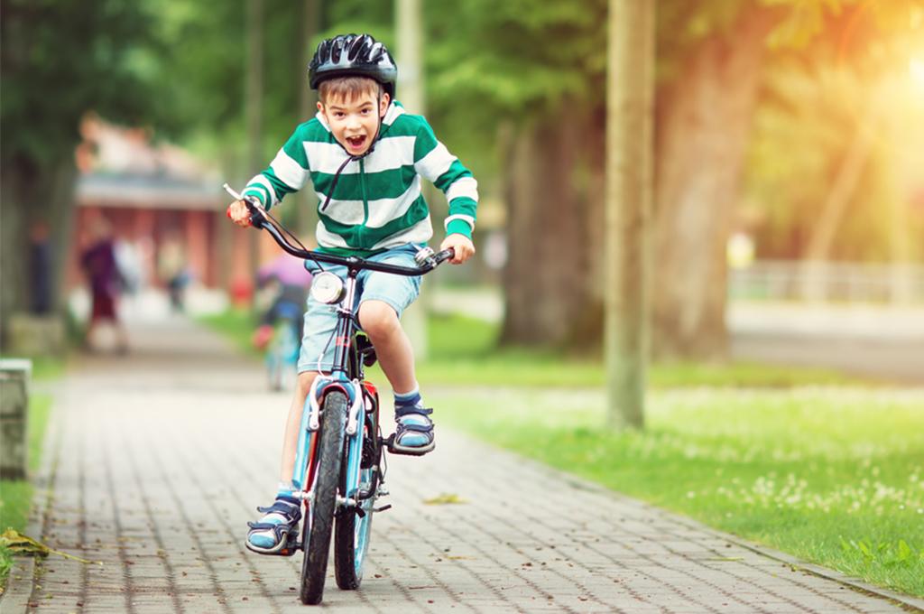 Счастливый мальчик катается на детском велосипеде
