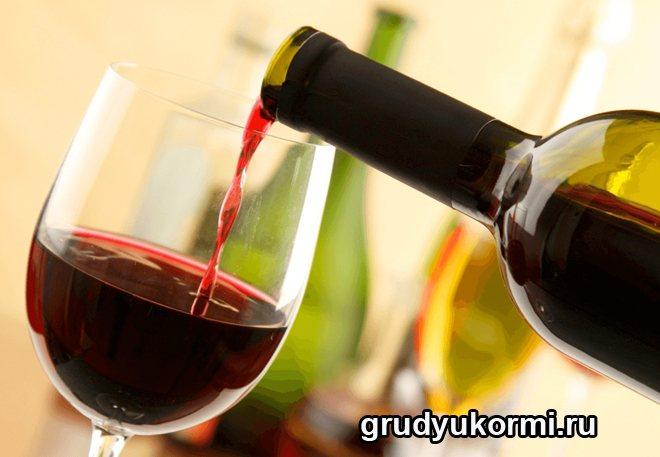 З пляшки наливають червоне вино у фужер