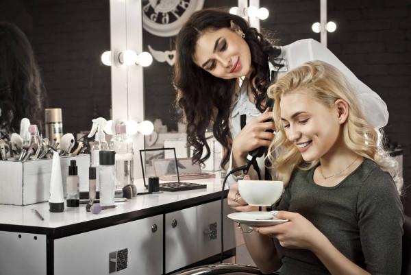 Молодая девушка в салоне красоты пьет вкусный кофе