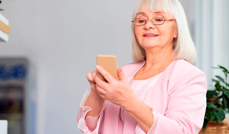 Бабуся сплачує комунальні послуги онлайн за допомогою мобільного телефону