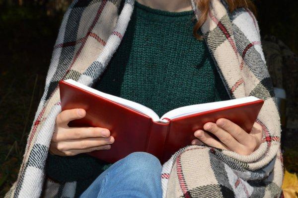 Дівчина читає книгу загорнувшись у теплий плед