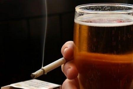Сигарета і келих пива в руці людини