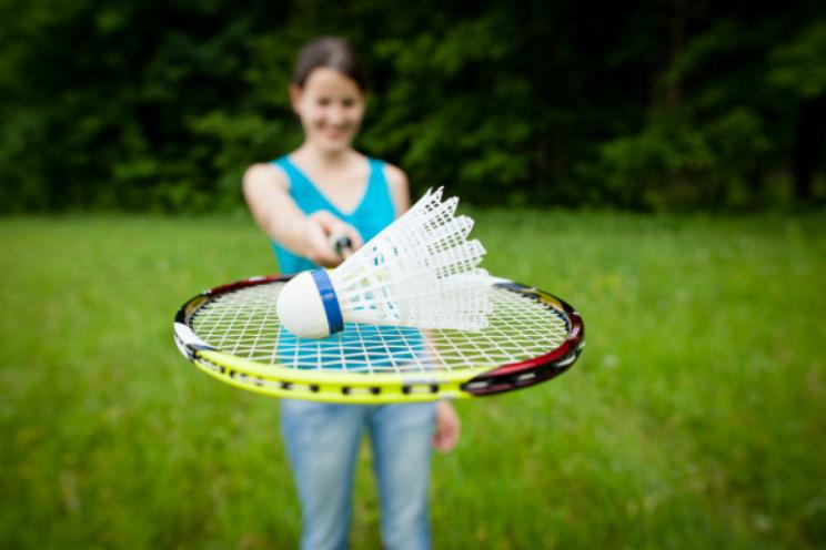 Спортсменка держит волан на профессиональной ракетке для бадминтона