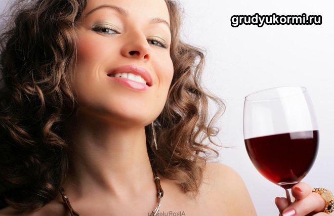 Жінка тримає фужер з червоним вином